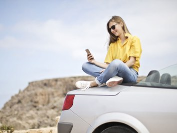 Woman sat on her car in the sun using her phone